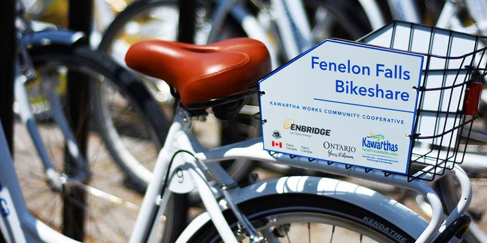 "Image of a bike saddle and basket reading ""Fenelon Falls Bikeshare"""